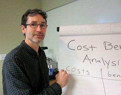 Photo of Rick Goggins demonstratng cost benefit analysis